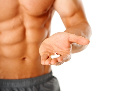 14036990 - close up of muscular man torso with hand full of pills on white